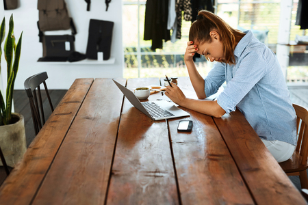 Business Woman Working On Laptop Computer At Cafe Table. Portrait Of Stressed , Depressed Female Having Headache, Head Pain. Freelance Work, Failure, People Communication Technology Concept Stock Photo