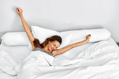 아침 일어나. 웃는 젊은 여자 깨어 완전 화이트 침구 '휴면'. 모델 침대에서 스트레칭. 소녀 침실에서 휴식, 거짓말. 건강한 수면, 라이프 스타일.  스톡 콘텐츠