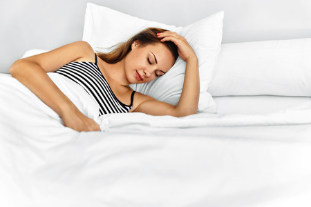 wellness sleepy: Healthy Lifestyle. Closeup Of Beautiful Young Woman Sleeping On White Bedding ( Linen ) In Bedroom In Morning. Girl Lying In Bed, Relaxing At Home. Healthy Sleep. Wellness, Health And Beauty Concept
