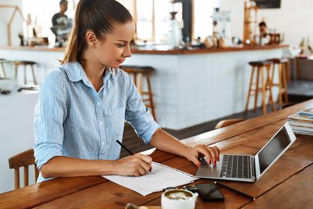 Lernen, Studieren. Portrait der schönen glücklichen Lächeln Studenten Frau mit Laptop-Computer, Notebook, Schreiben, Notizen An Cafe. Weiblich Freelancer arbeiten. Freie Mitarbeit, Geschäftsleute Konzept