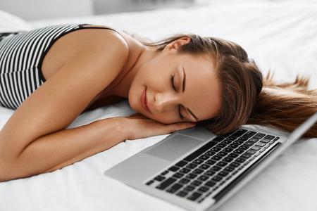 mujer en la cama: Mujer que se relaja con la computadora portátil. Retrato de detalle de hermosa sonriente de la muchacha de mentira soñoliento cuaderno cerca, del ordenador en cama en el país. Freelancer descanso después del trabajo. Tecnología de la comunicación. Concepto independiente
