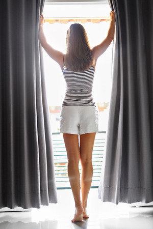 woman window: Morning. Beautiful Sexy Young Woman With Fit Slim Body Opening Curtains In Bedroom. Girl Standing Near Window At Home. New Day Concept. Wellness, Healthy Lifestyle.