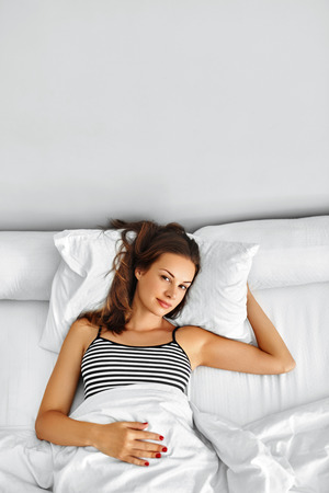 rested: Healthy Lifestyle. Beautiful Happy Smiling Woman Lying Fully Rested After Wake Up On White Bedding, Linen In Bedroom In Morning. Girl Relaxing In Bed At Home. Sleep, Wellness, Health, Beauty Concept