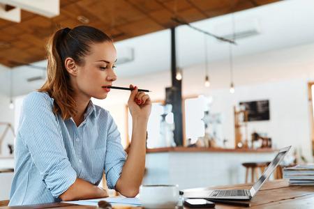 Aprender, Estudiar. Retrato de la mujer del estudiante que usa el ordenador Portátil, pensando en el café. Mujer de Trabajo Autónomo. Trabajo por cuenta propia, de negocios Concepto