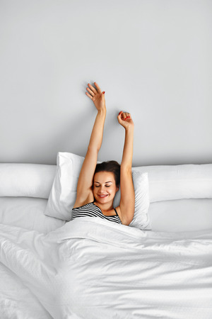 Morning Wake Up. Smiling Young Woman Waking Up Fully Rested On White Bedding. Model Stretching In Bed. Girl Lying, Relaxing In Bedroom. Healthy Sleep, Lifestyle. Wellness, Health, Beauty Concept Reklamní fotografie