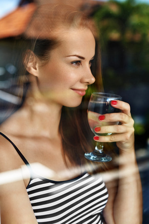 health woman: Drink Water. Closeup Happy Smiling Woman Drinking Fresh Refreshing Pure Water From Glass In Morning At Window. Health And Diet Concept. Healthy Lifestyle, Nutrition. Healthcare And Beauty. Hydration