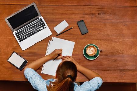 学習、勉強します。ラップトップ コンピューター、ノートブック、カフェのテーブルでノートを使用して学生の女性の平面図です。フリーランサー