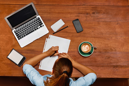 Learning, Studying. Top View Of Student Woman Using Laptop Computer, Notebook, Taking Notes At Cafe Table. Freelancer Girl Working. Freelance Work, Business People, Communication Technology Concept 스톡 콘텐츠