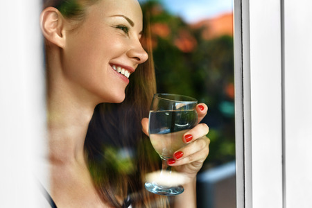 hydration: Drink Water. Closeup Happy Smiling Woman Drinking Fresh Refreshing Pure Water From Glass In Morning At Window. Health And Diet Concept. Healthy Lifestyle, Nutrition. Healthcare And Beauty. Hydration