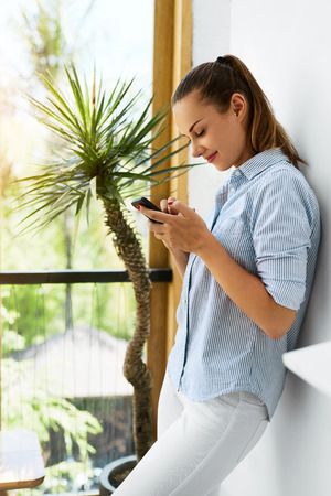 woman dialing phone number: Communication Technology. Portrait Of Beautiful Happy Smiling Freelancer Businesswoman Using Mobile Phone. Girl Typing Text Message On Smart Phone, Dialing Number. Woman Working. Business Concept
