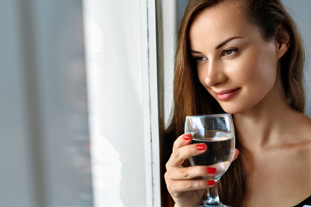 vasos de agua: Beber agua. Primer sonriente de la mujer feliz que bebe el agua dulce pura refrescante de Vidrio En la mañana en la ventana. Concepto de salud y la dieta. Estilo de vida saludable, nutrición. Cuidado de la salud y la belleza. Hidratación