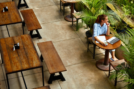 Learning, Studying. Portrait Of Beautiful Happy Smiling Student Woman Using Laptop Computer, Notebook, Writing, Taking Notes At Cafe. Female Freelancer Working. Freelance Work, Business People Concept