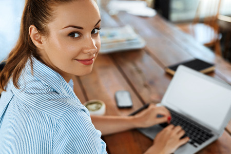 Femme d'affaires travaillant sur ordinateur portable au Cafe Table. Closeup Portrait Belle Heureuse Femme souriante Réussie Tapant Sur Clavier Notebook. Freelance Work, Concept de technologie de communication de personnes