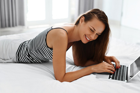 e commerce: Woman Shopping Online. Closeup Portrait Of Happy Beautiful Smiling Girl Blogging Using Laptop Computer Lying On Bed. Female Typing On Notebook Keyboard At Home. Communication Technology. E - Commerce