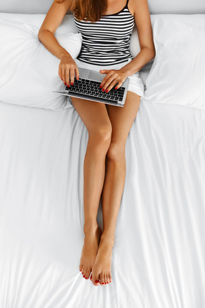 girl legs: Woman Using Computer At Home. Closeup View Of Female Freelancer With Long Fit Legs Chatting, Typing On Laptop, Relaxing On Bed. Girl Working On Pc, Notebook. Online Shopping. Communication Technology. Stock Photo