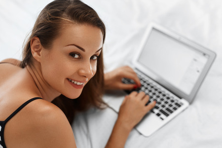 commerce communication: Woman Shopping Online. Closeup Portrait Of Happy Beautiful Girl Blogging Using Laptop Computer Lying On Bed. Female Typing On Notebook At Home Smiling At Camera. Communication Technology. E - Commerce