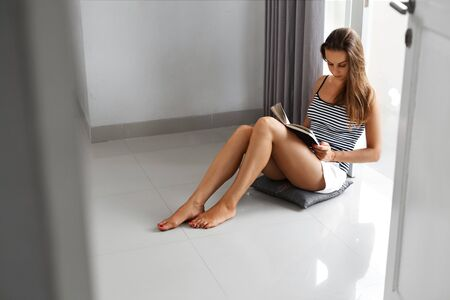 relaxing at home: Reading Books. Beautiful Young Woman Reading Book Or Studying On Floor By Window. Girl Relaxing, Enjoying Book At Home. Recreational Leisure Activity. Hobby. Power Of Self Education, Knowledge.