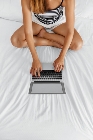 chicas comprando: Woman Using Computer At Home. Closeup View Of Female Freelancer With Long Fit Legs Chatting, Typing On Laptop, Relaxing On Bed. Girl Working On Pc, Notebook. Online Shopping. Communication Technology. Foto de archivo