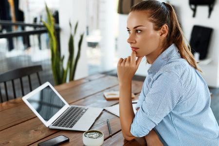 学習、勉強します。カフェでのラップトップ コンピューター、ノートブック、思考を使用して学生の美しい女性の肖像画。女性フリーランス作業。