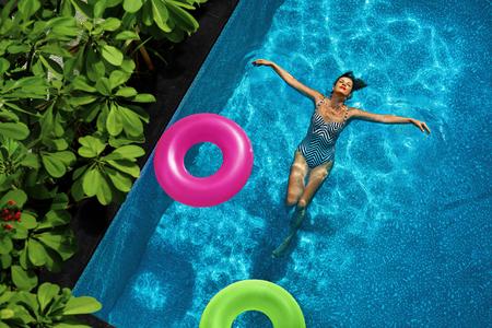 lifestyle: Vacances d'été. Sexy jeune femme heureuse Avec Perfect Fit Body In Fashion Swimsuit vacances Jouissant, Float Swim Anneaux flottants Dans l'eau de piscine A Tropical Resort. Style de vie sain. Bien-être