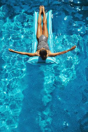 夏の休暇。フィットのボディ、水着は日光浴、健康な皮膚と美しいセクシーな幸せな笑顔の女性は、スイミング プールの水でリング フロート泳ぐ空