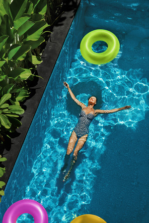 float: Summer Relax. Beautiful Carefree Happy Young Woman With Sexy Body In Swimsuit Having Fun With Colorful Float Swim Rings Floating In  Swimming Pool Water. Summertime Travel Holidays Vacation. Freshness Stock Photo