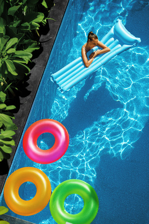 float: Summer Fun On Holidays Travel Vacation. Beautiful Sexy Young Woman Relaxing, Enjoying Summertime. Colorful Inflatable Float Rings, Air Mattress Floating In Swimming Pool Water. Lifestyle, Recreation