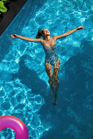 frescura: El verano se relaja. Joven y bella mujer despreocupada feliz con cuerpo Sexy en traje de baño que se divierte con flotador de flotador colorido flotando en la piscina de agua. El verano viaje vacaciones de vacaciones. Frescura Foto de archivo