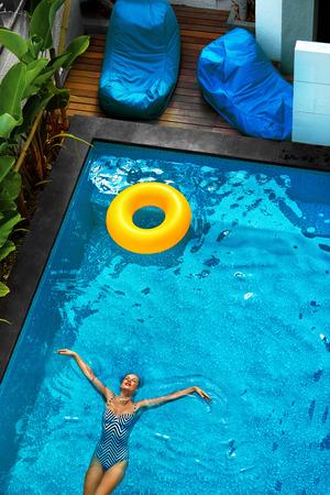 schwimmring: Sommerferien. Sexy glückliche junge Frau mit perfekten Fit Körper In Mode Badeanzug Urlaub genießen, Schwimmer Schwimmen Ringe Floating In Pool Wasser im tropischen Resort. Gesunder Lebensstil. Wellness