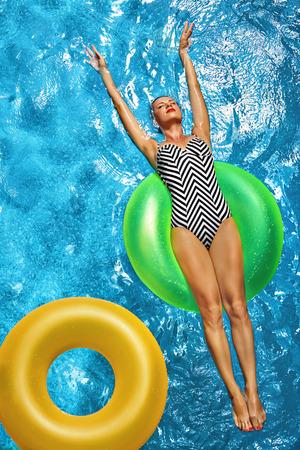 Vacances d'été. Belle Sexy femme souriante avec Perfect Fit Body, une peau saine en maillot de bain Bain de soleil, Flotter sur Float Bouée Dans l'eau de piscine. Jouissance. Beauté, Bien-être. Récréation Banque d'images - 55831656