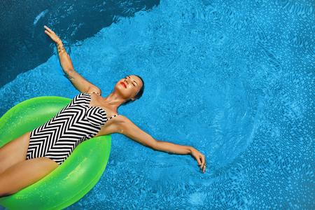 Vacaciones de verano. Hermosa atractiva Mujer Sonriente Con ajuste perfecto del cuerpo, la piel sana en traje de baño que toma el sol, flotando en el anillo de la nadada del flotador en piscina de agua. Disfrute. Belleza, Bienestar. Recreación
