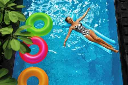 El verano se relaja. Joven y bella mujer despreocupada feliz con cuerpo Sexy en traje de baño que se divierte con flotador de flotador colorido flotando en la piscina de agua. El verano viaje vacaciones de vacaciones. Frescura