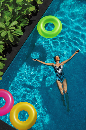 health woman: Summer Relax. Beautiful Carefree Happy Young Woman With Sexy Body In Swimsuit Having Fun With Colorful Float Swim Rings Floating In  Swimming Pool Water. Summertime Travel Holidays Vacation. Freshness Stock Photo