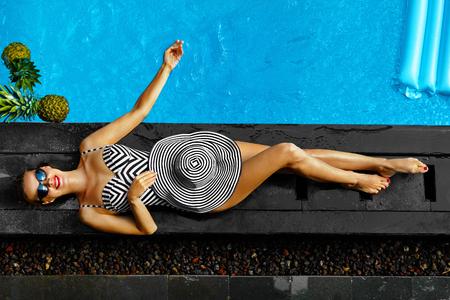"""Moda de verão de mulher. Menina de sorriso """"sexy"""" feliz com corpo do ajuste, pés longos, pele saudável no biquini, chapéu de Sun, óculos de sol que toma sol pela piscina em férias dos feriados do curso. Beleza, bem-estar, estilo de vida"""