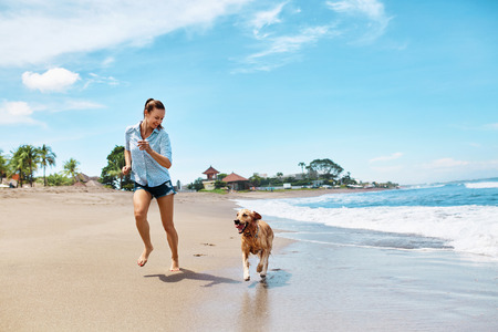 pets: Summer Fun On Beach. Beautiful Happy Woman Running With Her Dog, Golden Retriever, Pet On Wet Sand In Sea Water. Holidays Vacations At Tropical Resort. Summertime Travel Concept. Stock Photo