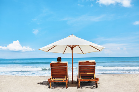 loungers: Summer Beach Relaxation On Holidays Vacations. Woman Relaxing On Beach Lounge Chairs Under Tent By Sea. Tropical Resort Relax On Deckchairs, Sun Loungers Under Umbrella. Summertime. Enjoyment Concept