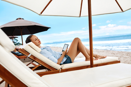 relaxing beach: Summer Relaxation. Beautiful Woman Reading E-Book, Relaxing On Sun Lounger, Deck Chair Under Umbrella, Tent On Beach By Sea. Summertime. Holiday Vacations. Leisure, Recreation, Enjoyment Concept