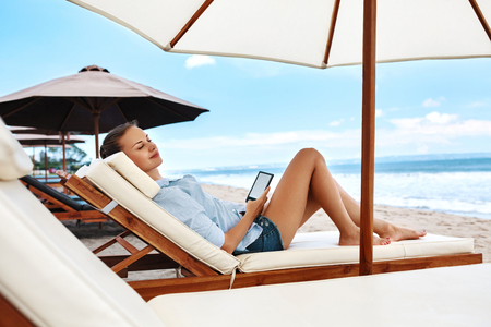 beach holiday: Summer Relaxation. Beautiful Woman Reading E-Book, Relaxing On Sun Lounger, Deck Chair Under Umbrella, Tent On Beach By Sea. Summertime. Holiday Vacations. Leisure, Recreation, Enjoyment Concept