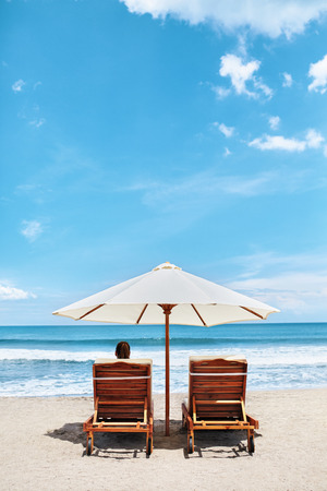 summer holidays: Summer Beach Relaxation On Holidays Vacations. Woman Relaxing On Beach Lounge Chairs Under Tent By Sea. Tropical Resort Relax On Deckchairs, Sun Loungers Under Umbrella. Summertime. Enjoyment Concept