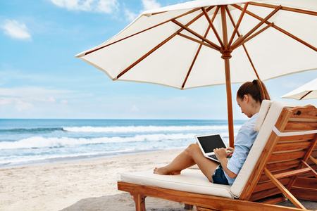 Work At Beach. Successful Freelancer Business Woman Working Online In Internet On Laptop Computer, Typing On Keyboard Relaxing By Sea. Freelance Outdoors Work. People Communication, Technology Concept Foto de archivo