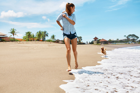 Summer Fun On Beach. Beautiful Happy Woman Running With Her Dog, Golden Retriever, Pet On Wet Sand In Sea Water. Holidays Vacations At Tropical Resort. Summertime Travel Concept. Stock Photo
