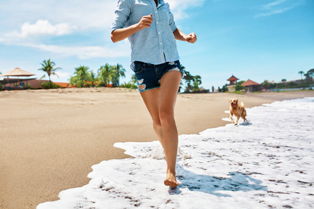 fetch: Summer Fun On Beach. Beautiful Happy Woman Running With Her Dog, Golden Retriever, Pet On Wet Sand In Sea Water. Holidays Vacations At Tropical Resort. Summertime Travel Concept. Stock Photo