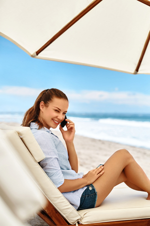 mobile telephone: Mobile Communication. Beautiful Happy Smiling Woman Using Cell Phone, Talking On Telephone, Lying On Sun Lounger On Beach. Summer Vacations. Freelance Business Work. Connection Technology Concept Stock Photo