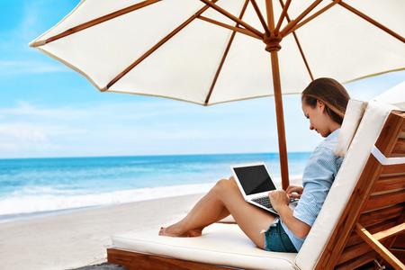Werk aan het strand. Succesvolle freelancer zakenvrouw werkt online in internet op laptopcomputer, typen op toetsenbord ontspannen door zee. Freelance buitenshuis werken. Mensencommunicatie, Technologieconcept