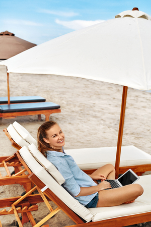 relaxing beach: Summer Work. Portrait Of Beautiful Happy Smiling Woman Relaxing On Sun Lounger, Using Laptop Computer Working Online In Internet At Beach By Sea. Freelance Work. Business People, Communication Concept