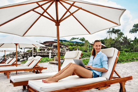 Business Woman Working Online On Laptop Computer Lying On Sun Loungers At Beach. Portrait Happy Successful Smiling Freelancer. Freelance Distance Internet Work, People Communication Technology Concept