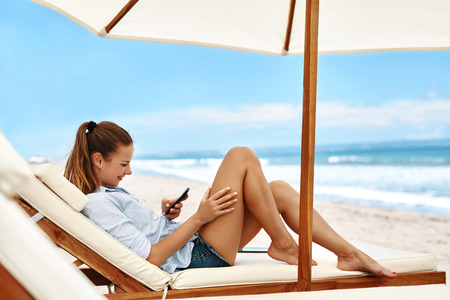 Mobile Communication. Portrait Of Beautiful Happy Smiling Woman Using Cell Phone, Dialing Number, Lying On Deck Chair On Beach. Summer Holidays Vacations. Freelance Business Work. Connection Concept