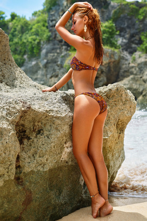 sexy butt: Summer Beach Vacation. Beautiful Healthy Woman With Fit Body, Sexy Butt And Hips In Fashion Bikini Posing By Sea Rock By Ocean. Happy Girl Sunbathing For Tan. Model Relaxing At Luxury Resort
