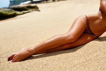 Piernas de la mujer en la playa. La muchacha hermosa atractiva con el ajuste delgado de cuerpo, sana la piel sedosa Sun bronceada suave y patas largas depilada que se relaja en la arena. Mujer En Bikini tomando el sol en verano. Parte del cuerpo humano