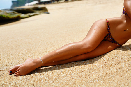 Woman Legs On Beach. Beautiful Sexy Girl With Slim Fit Body, Healthy Smooth Silky Sun Tanned Skin And Long Depilated Legs Relaxing On Sand. Female In Bikini Sunbathing In Summer. Human Body Part